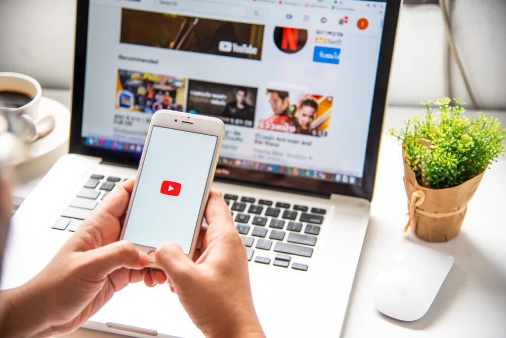 A picture of someone holding a mobile phone with the youtube logo on it, in front of a laptop which is displaying a list of video thumbnails on Youtube.