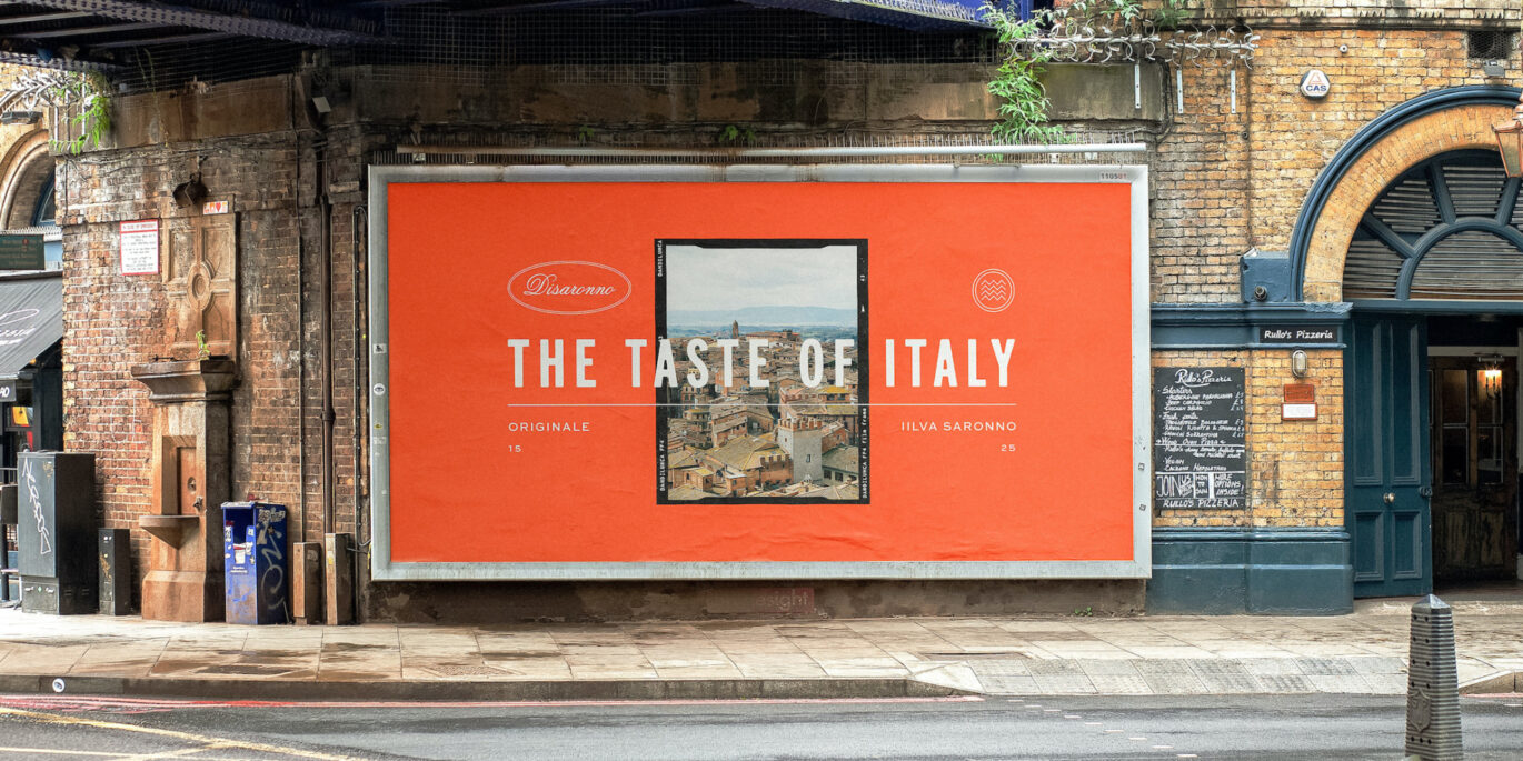 An image of a billboard advert featuring a bright orange poster with the new Disaronno font overlaid onto it and a picture of the Italian countryside in the middle. The text says The Taste of Italy - Disaronno's tag line.