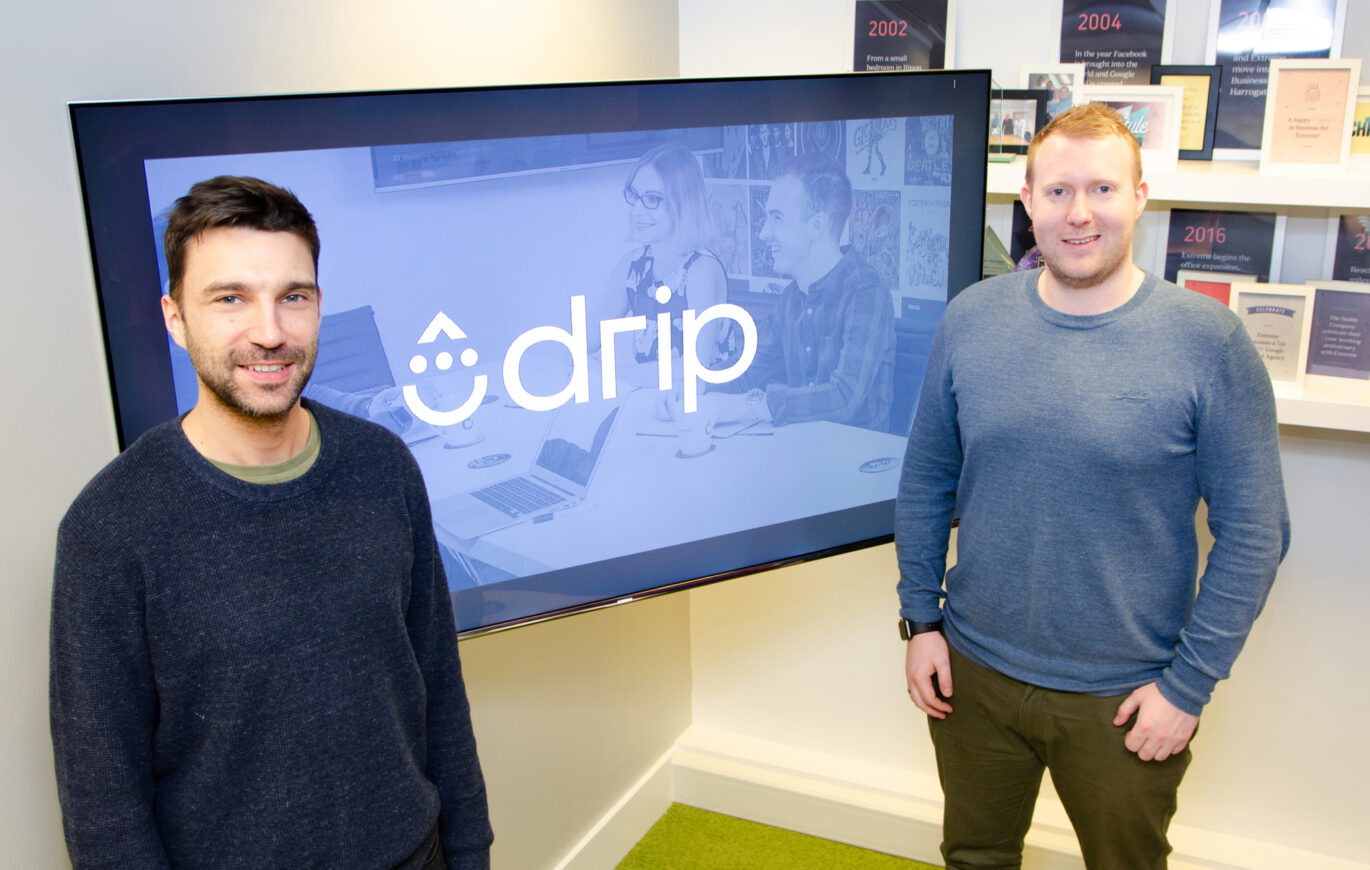 Two men stood in front of the Drip logo on a TV screen.