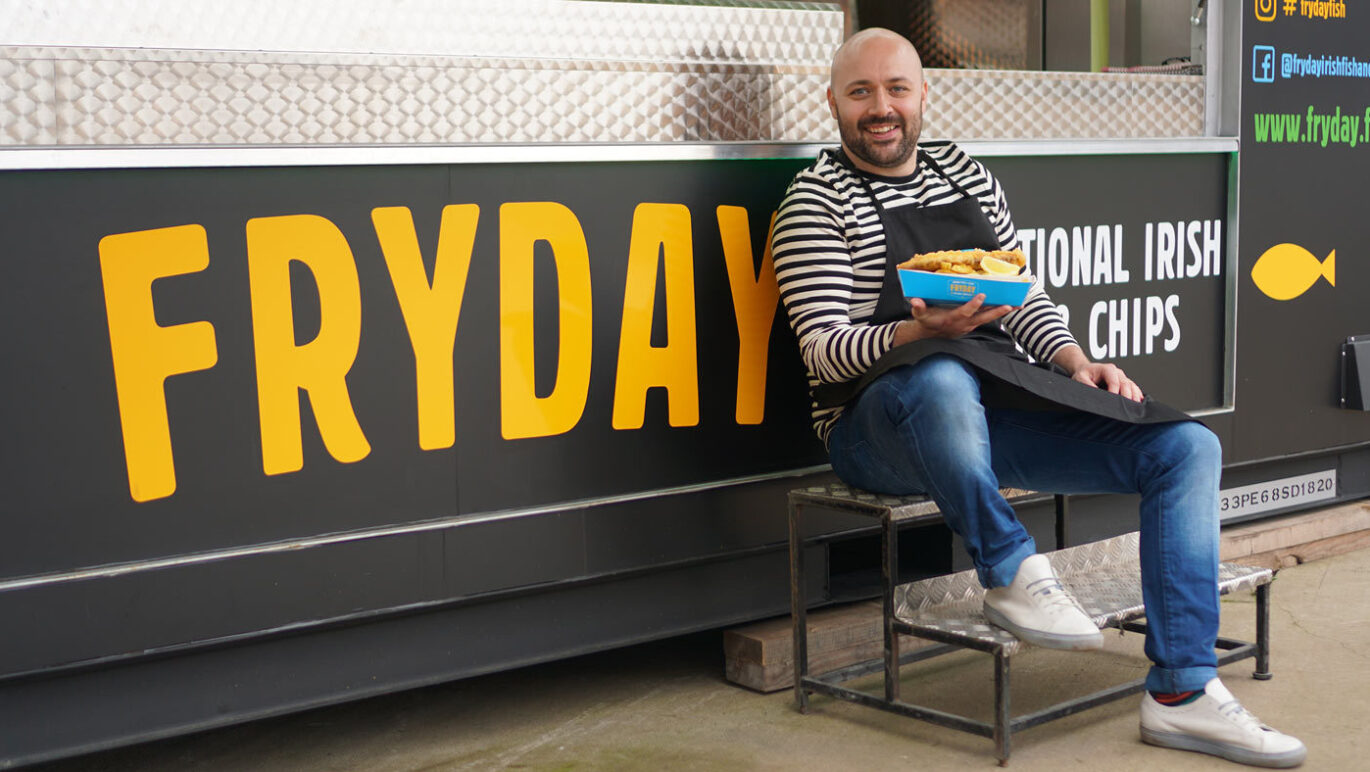 A man sat in front of a fish and chip stand, holding fish and chips and smiling.