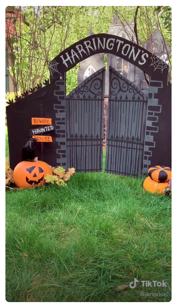 A haunted house made out of a cardboard box, surrounded by carved pumpkins