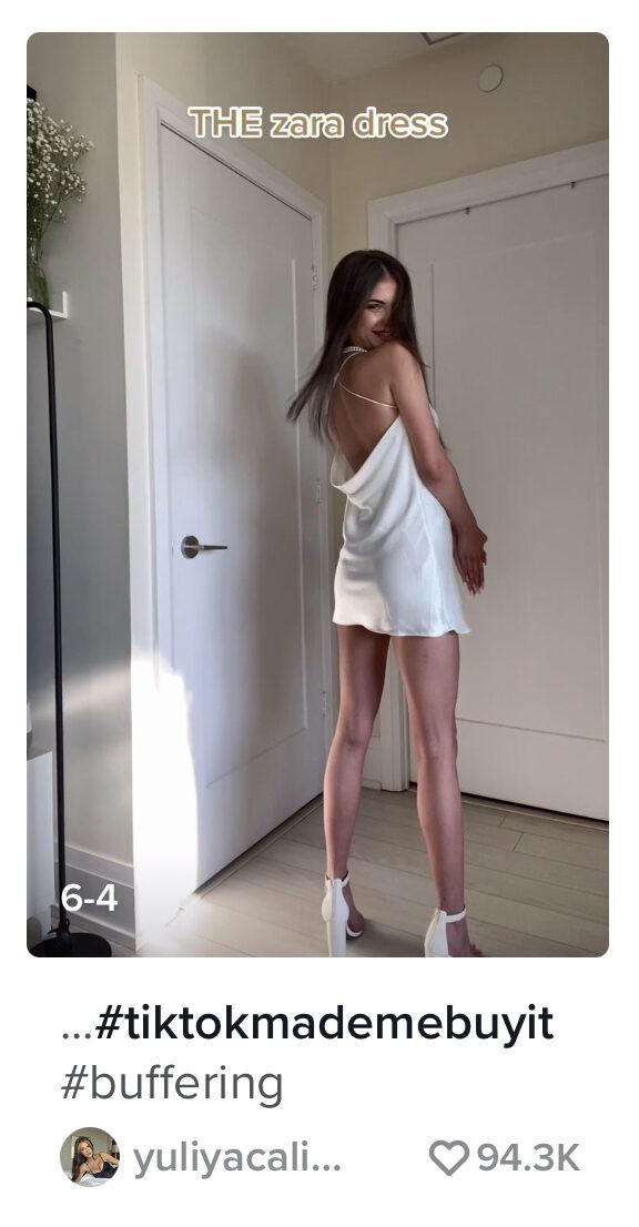 A screenshot of a woman wearing a cream, silk dress.