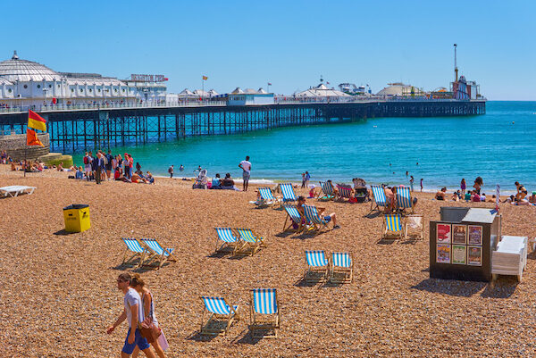 A sunny beach, with lots of people sat sunbathing and playing in the sea.