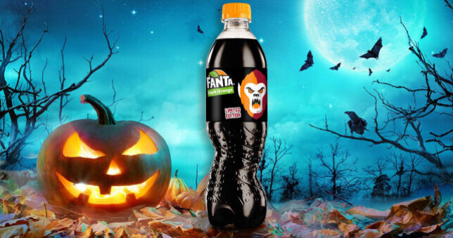 An image of a pumpkin next to a bottle of black fanta with a spooky background of a dark forrest.
