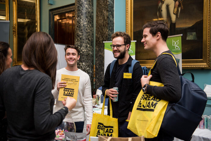 Four people talking at a conference holding yellow bags with the Bread and Jam logo on it.