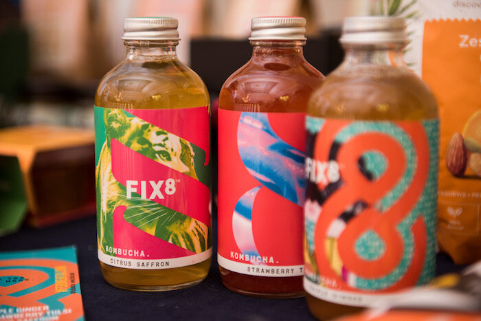 Three bottles of Fix 8 Kombucha in different flavours with colourful, modern graphics on the labels.
