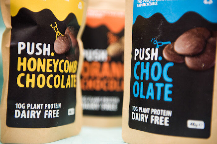 Packets of plant-based chocolate high in protein in plain and honey comb flavours